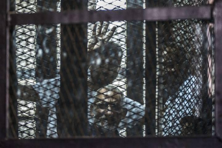 El líder de los Hermanos Musulmanes, Mohamed Badie, hace gestos desde la celda en la que atiende su juicio en la prisión de Tura (Egipto), el 3 de agosto de 2014