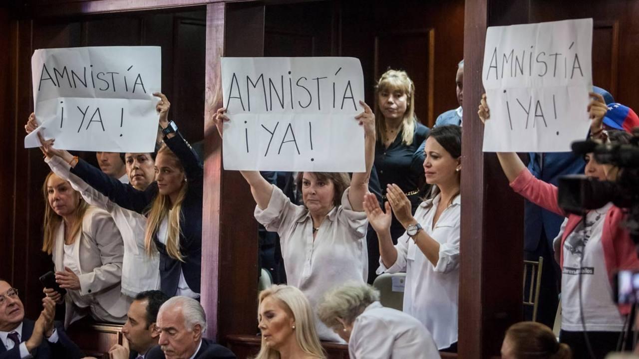 Lilian Tintori, Mitzi Capriles y Patricia Ceballos muestran carteles pidiendo una ley de amnistía durante la instalación de la Asamblea Nacional.