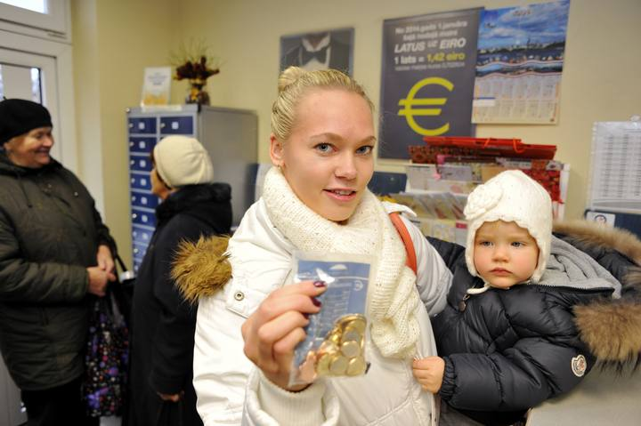 Linda Grabouska y su hija Jasmina muestran una bolsa con monedas de euro letonas