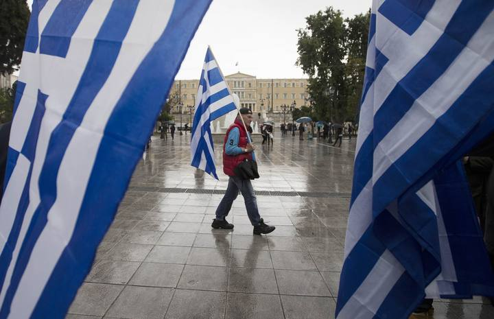 Man holding a Greek flag walks on central Syntagma square as the parliament is seen in the background, in Athens