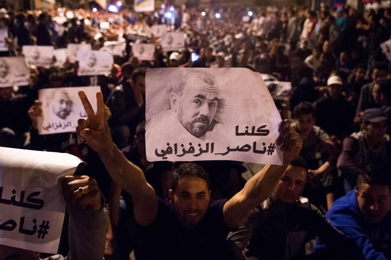Manifestantes agitan pancartas con el rostro del lider de las protestas en el Rif, Nasser Zafzafi.