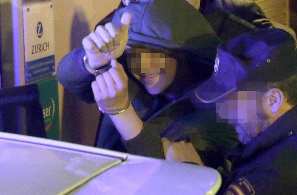 El menor de edad que agredió a Rajoy, saluda mientras es detenido.