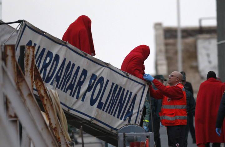 Un miembro de Cruz Roja junto a varios de los 26 inmigrantes que han llegado al puerto pesquero de Almería tras ser rescatados por Salvamento Marítimo en una patera la isla de Alborán.