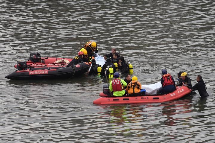 Miembros de los equipos de rescate recuperan el cuerpo de una de las víctimas del accidente de avión en el río Jilong en Taiwan