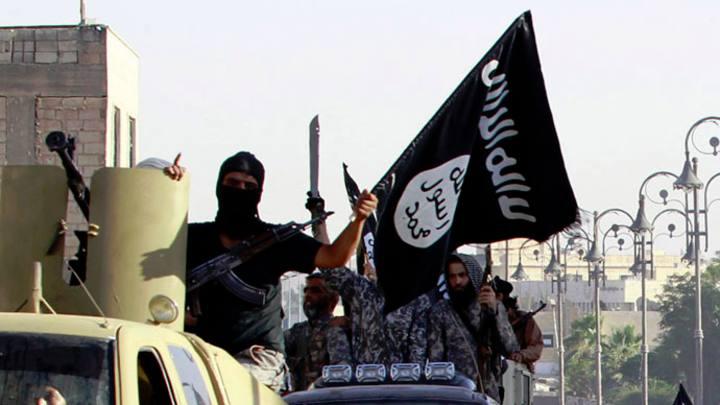 Un miliciano yihadista blandiendo una bandera del Estado Islámico