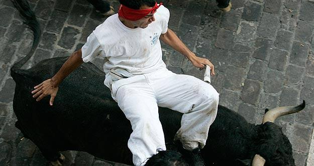 Un mozo a lomos de un toro en uno de los encierros de San Fermín