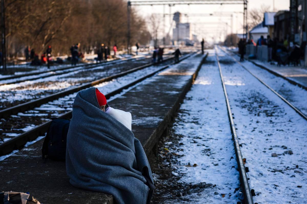 Una mujer abraza a su hijo mientras espera un tren bajo un frío invernal en las vías de Presevo, en Serbia.