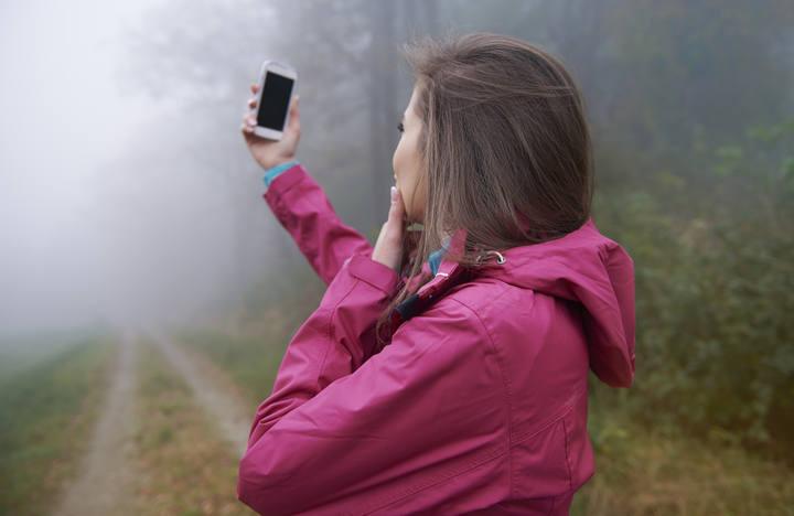 Una mujer busca cobertura con su móvil en un bosque.