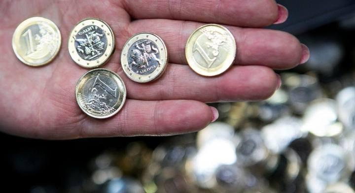 Una mujer muestra los euros con el caballero lituano Vytis