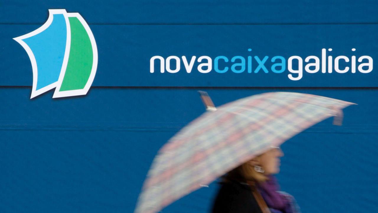 Una mujer pasa por delante de una sucursal de Novacaixagalicia