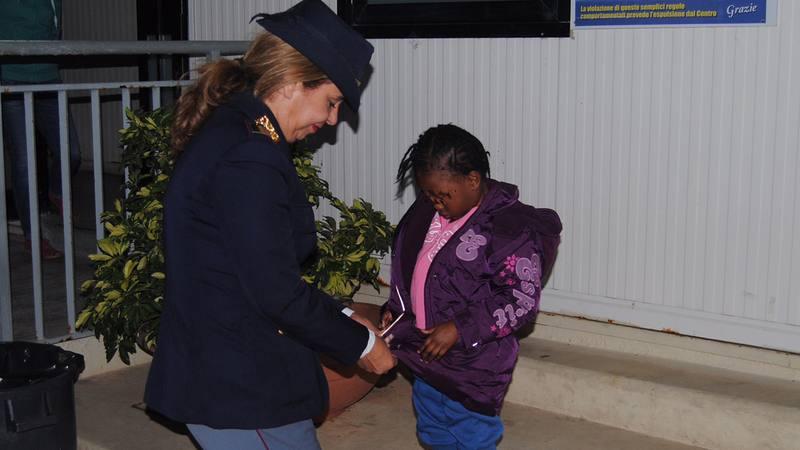 La niña marfileña Oumoh es atendida por la agente de policía María Volpe en Lampedusa