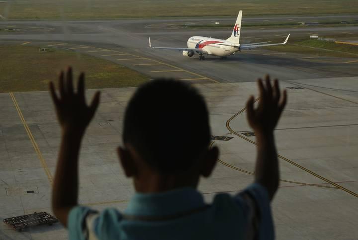 Un niño observa un avión de Malaysia Airlines en el aeropuerto de Kuala Lumpur