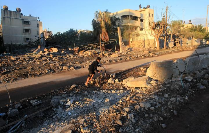 Un niño palestino empuja su bicicleta en un barrio arrasado por los bombardeos.