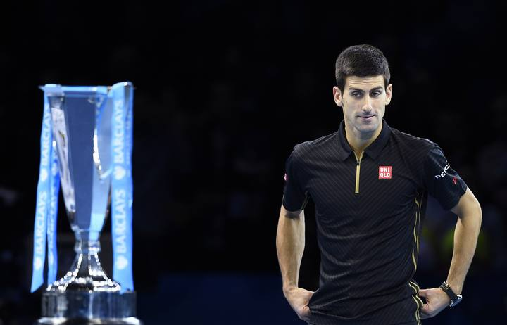 Novak Djokovic of Serbia looks at the trophy after Roger Federer of Switzerland forfeited due to injury in the men's singles final at the ATP World Tour Finals at the O2 in London