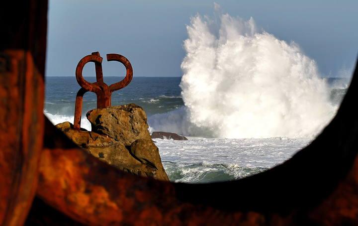 Una ola rompe junto al Peine de Viento, Obra de Eduardo Chillida, en San Sebastián.
