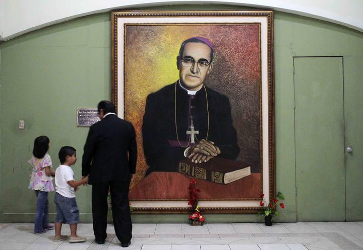 Un padre y su hija observan un retrato de Monseñor Oscar Arnulfo Romero, arzobispo de San Salvador, en la catedral de San Salvador.