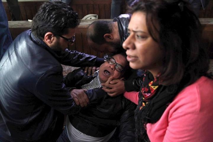 El padre de uno de los condenados llora al oir el veredicto de su hijo en un tribunal de El Cairo.