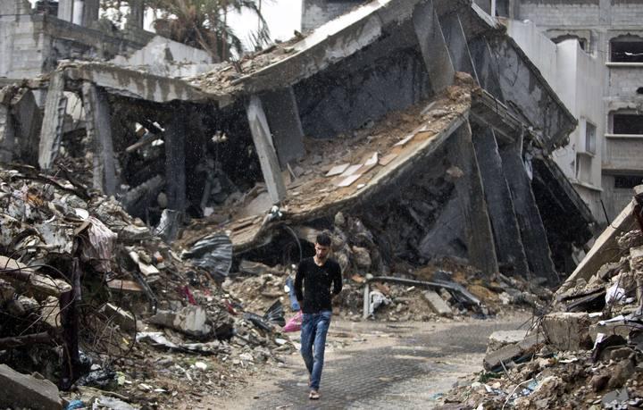 Un palestino pasea entre los escombros de los edificios destruidos en la útlima operación militar israelí en Gaza.