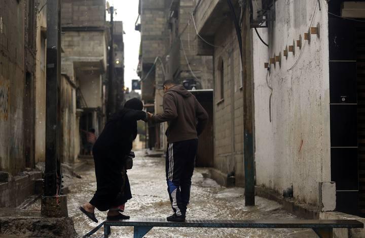 Palestinos intentan salvar una calle inundada en la ciudad de Gaza, el 27 de noviembre