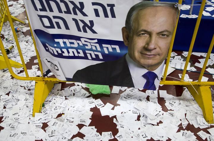 Papeletas electorales frente a un cartel de Benjamín Netanyahu, en Tel Aviv, Israel