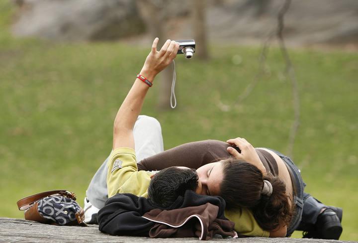 Una pareja de jóvenes se besa en un parque