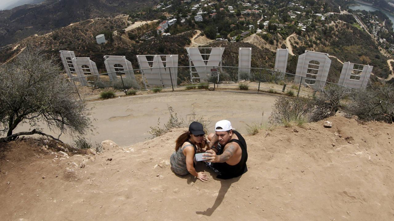 Una pareja se fotografía con el letrero de Hollywood en Los Ángeles