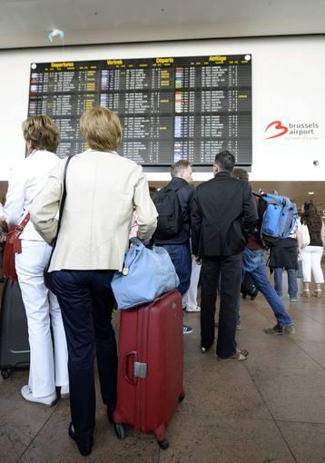 Pasajeros mirando los paneles de información del aeropuerto de Bruselas