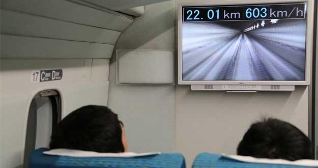 Pasajeros en el viaje de prueba del Maglev japonés observando la pantalla que marca 603 km/h de velocidad.