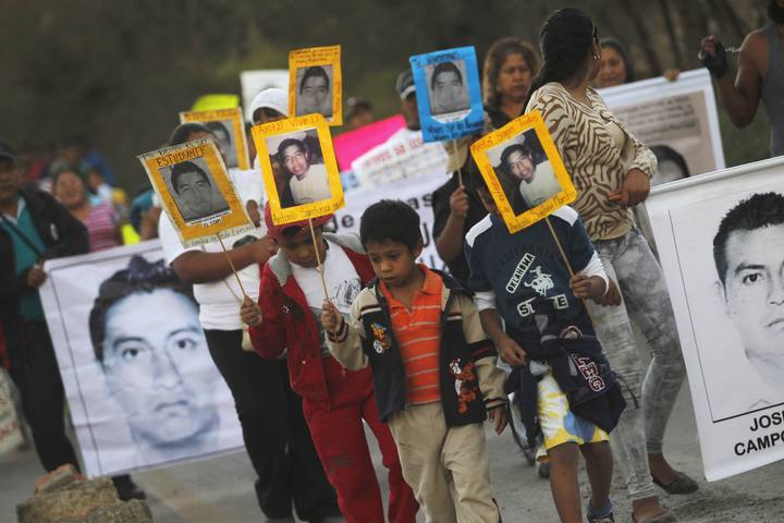 People, some carrying a picture of one of the 43 missing students of the Ayotzinapa Teacher Training College Raul Isidro Burgos, participate in a demonstration to demand justice for the missing trainee teachers, in Tixtla, on the outskirts of Chilpan