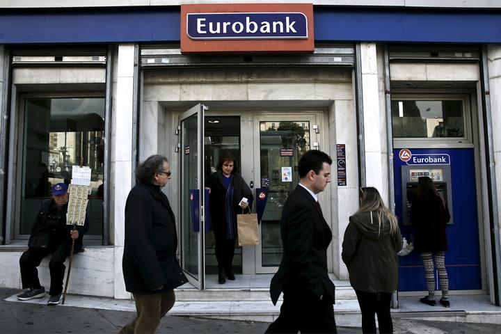 Una persona retira dinero de un cajero de una sucursal de Eurobank en Atenas