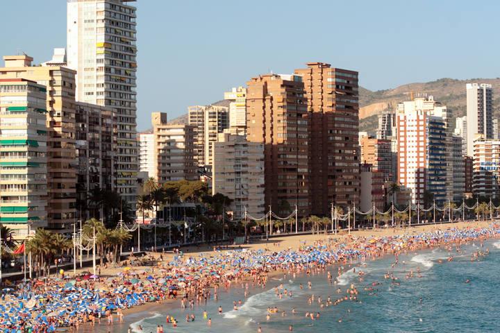 Playa de Benidorm repleta de bañistas y personas tomando el sol.