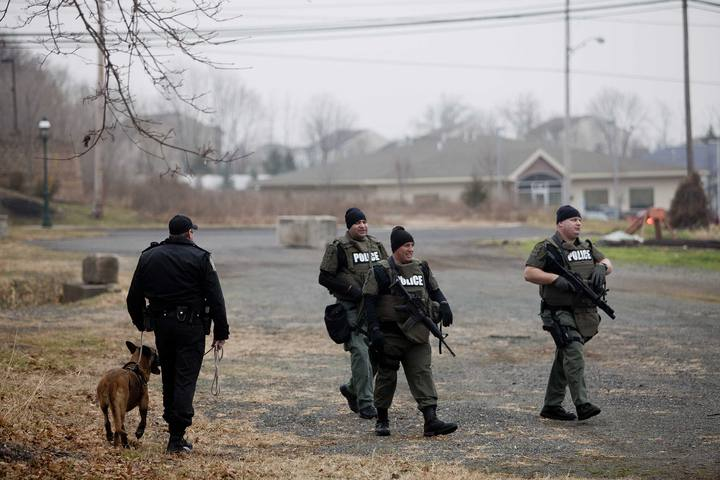Police officers search for Bradley William Stone an Iraq war veteran suspected of fatally shooting and stabbing six family members in Pennsburg Pennsylvania