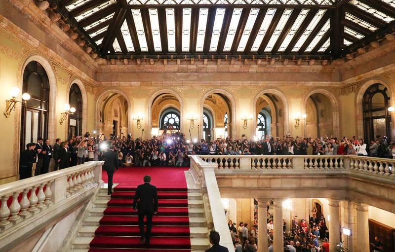 Es el momento en el que Carles Puigdemont sube las escaleras del Parlamento de Cataluña rodeado de prensa