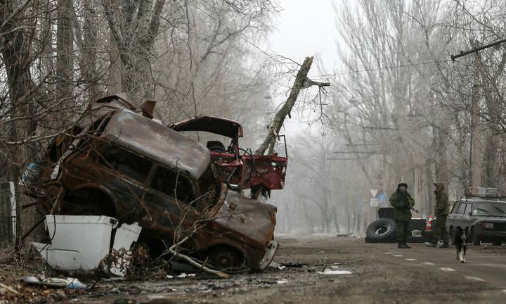 Pro-Russian separatists stand guard next to cars damaged during fighting between pro-Russian rebels and Ukrainian government forces near Donetsk Sergey Prokofiev International Airport, eastern Ukraine