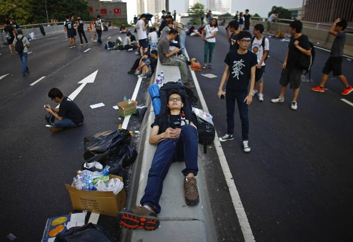 Protesters sleep as they block a street outside the government headquarters in Hong Kon