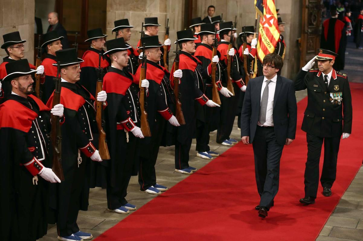 Puigdemont pasa revista a los Mossos d'Esquadra a su llegada al Palau de la Generalitat para tomar posesión de su cargo.