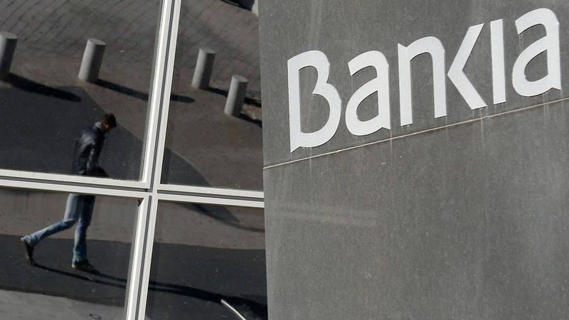 Reflejo de un joven transeúnte en los cristales de la sede de Bankia en las Torres Kio de Madrid