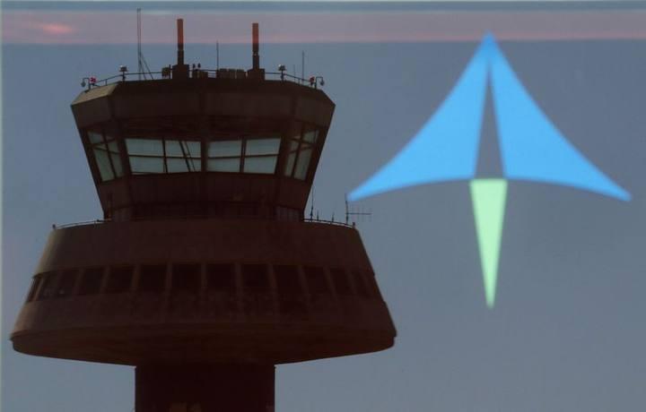 Reflejo de una torre de control sobre un cristal con el logo de AENA