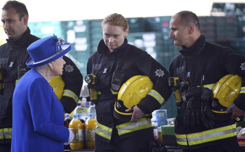 La reina Isabel II conversa con bomberos durante una reunión con residentes de la torre Grenfell en Londres.