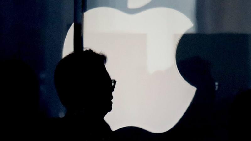 Silueta de un hombre frente a un logotipo de Apple en una tienda en Tokio