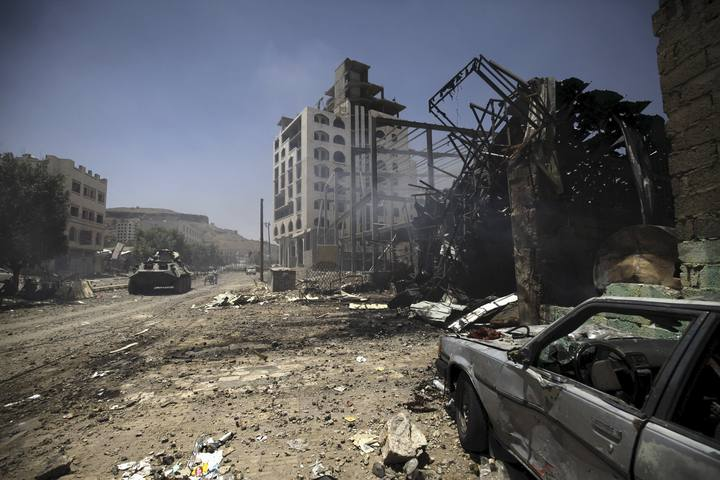 Smoke is seen at a damaged street, caused by an April 20 air strike that hit a nearby army weapons depot, in Sanaa