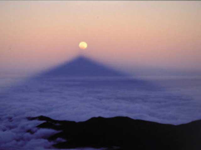Cuando el eclipse lunar se produce al amanecer o al atardecer, la sombra del Teide se alinea con la Luna.