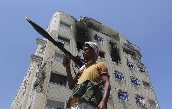 A Southern Popular Resistance fighter secures a street during fighting against Houthi fighters in the Dar Saad district of Yemen's southern port city of Aden