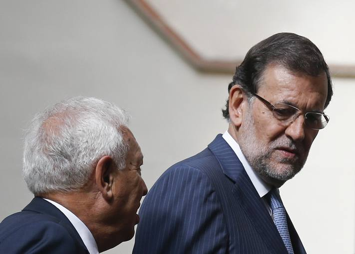 Spanish Prime Minister Mariano Rajoy listens to Foreign Minister Jose Manuel Garcia-Margallo after posing for a family photo in Madrid, during an international conference on stability and development in Libya