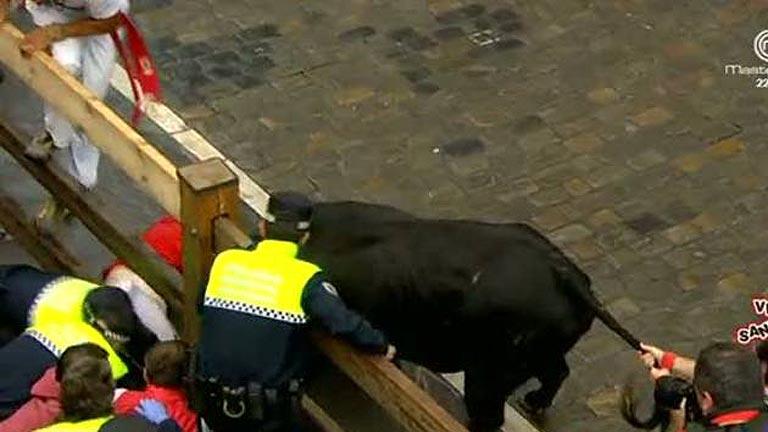 Un toro negro rezagado cornea a dos mozos