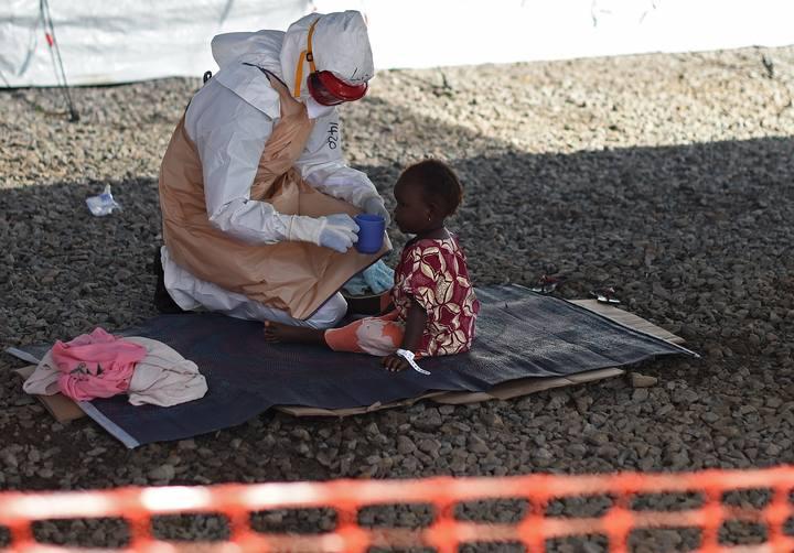 Un trabajador sanitario atiende a un niño en el centro de tratamiento contra el ébola de Kenama, en Sierra Leona