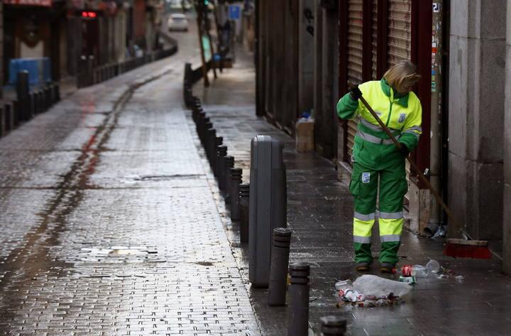 Una trabajadora de los Servicios de Limpieza de Madrid recoge basura