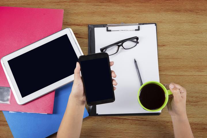 Una trabajadora con un smartphone y una tableta.