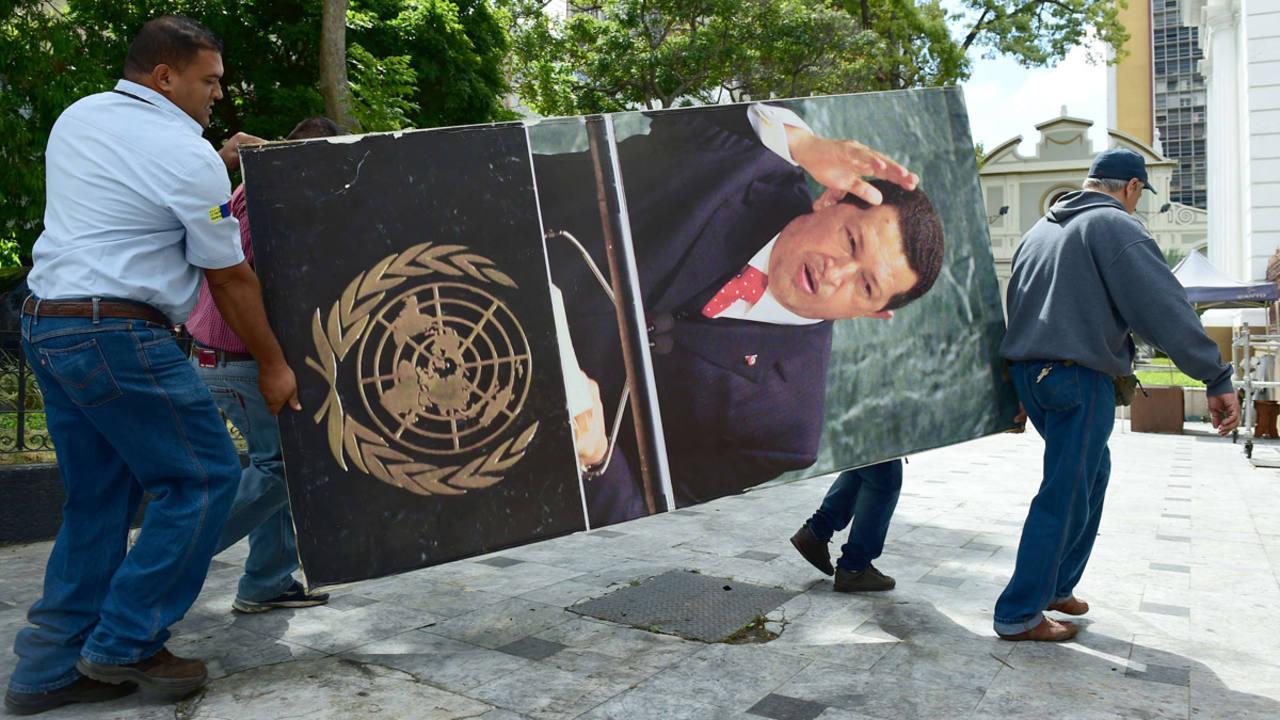 Trabajadores de la Asamblea Nacional retiran las imágenes del expresidente Chávez del edificio.