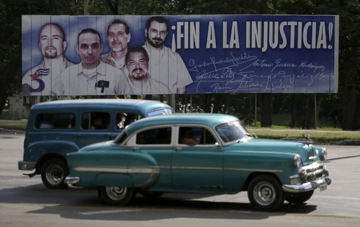 """Unos coches pasan por delante de un cartel con la imgan de los cinco prisioneros cubanos de la red """"La Avispa"""", encarcelados en EE.UU. por espionaje."""